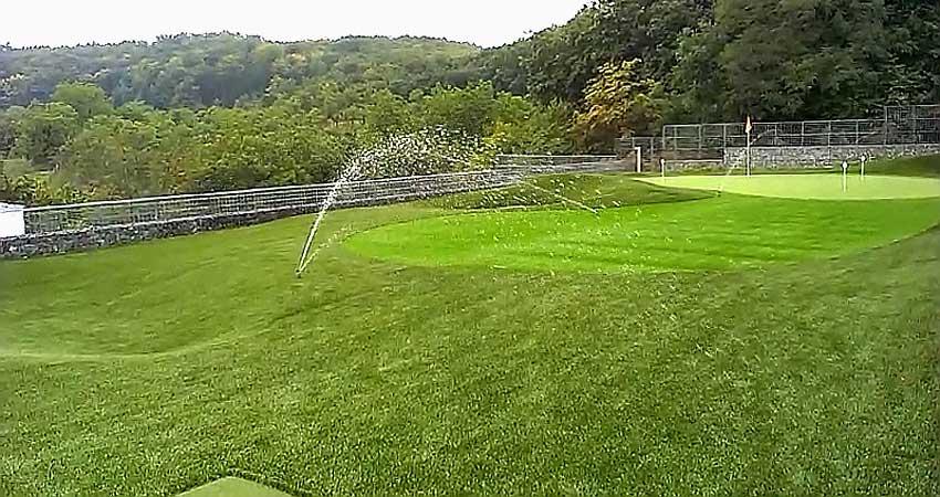 Kropení umělého povrchu golfového hřiště.