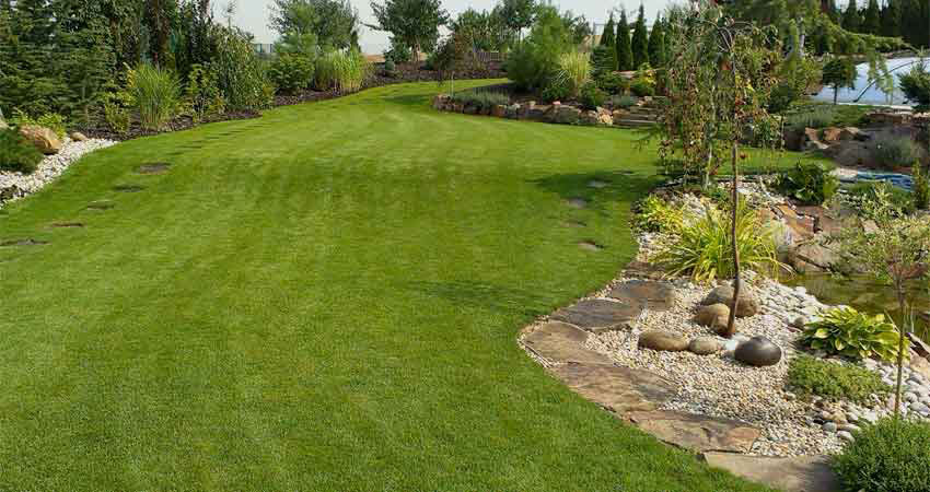 Nádherná zahrada s perfektním trávníkem zavlažovaným postřikovači s rotační tryskou.